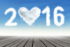 Cloud shaped numbers 2016 on the sky. Photo of cloud shaped numbers 2016 and heart symbol on the sky above wooden floor. New year concept Stock Images