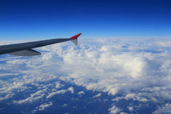 Cloud sky view from air plane window next to a wing Stock Image