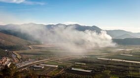 Cloud of smoke over the valley Stock Photos