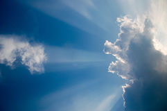 Cloud with sun rays and a small airplane. This picture shows a blue sky with a cloud and sun rays Stock Image
