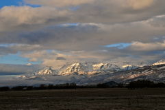 Cloud surround. Clouds surrounding a snow covered mount Timpanogos with sun spots peaking through Stock Photography
