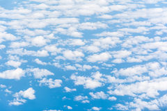 Cloud texture wallpaper. View of blue sky and cloudy field from airplane window. Stock Photo