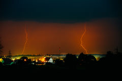 Cloud to Ground Electric Lightning behind house roof tops Stock Photo