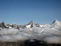 Cloud Walker. Ober Gabelhorn, Zinalrothorn & Weisshorn, view from Breithorn Glacier, Zermatt, Switzerland royalty free stock photography