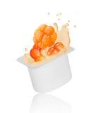Cloudberry falling into yogurt splash in plastic packing Stock Images