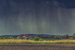Cloudburst over village Stock Photo