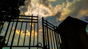 Clouded blue sky. And metal gate, daylight, yellow clouds stock photos
