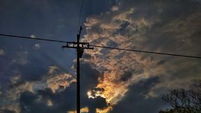 Clouded blue sky. During sunrise,yellow clouds,pole royalty free stock image