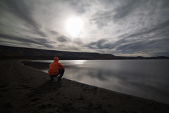 Clouded night. A moonlit but cloudy night on the shore of Kleifarvatn, Iceland. A man is kneeling on the shore and looking out on the lake Stock Photos