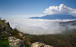 Cloudes over mountains Stock Images