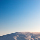 Cloudless blue sky above snow-covered hillside. Royalty Free Stock Photos