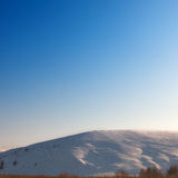 Cloudless blue sky above snow-covered hillside. Royalty Free Stock Image