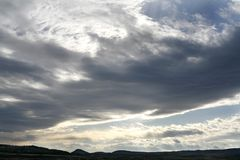 Clouds. Sunlight streams under a large bank of clouds Royalty Free Stock Photography
