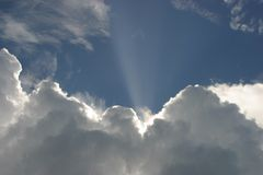Clouds. Peeking sunbeam from behind clouds royalty free stock image