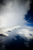 Into the clouds. Plane flying into a large white cloud in the air Stock Photography