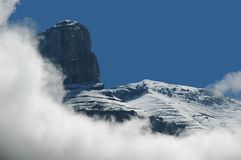 Among the clouds. Huge rock formations has just emerged from behind the clouds. Dare anybody reach the summit Stock Photo