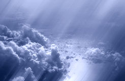In the Clouds. Shot of white puffy clouds with sun rays shining through above the sea royalty free stock photography