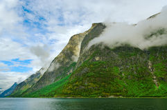 Clouds above fjord`s mountains. Royalty Free Stock Images