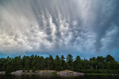 Clouds above forest lake Stock Photo