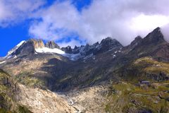 Clouds above a snowy mountain above a glacier Stock Photos