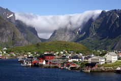 Clouds above village on Lofoten islands. Clouds above fishermans cabins and harbour of Reinebringen on Lofoten islands, Norway with mountains in the background Stock Image