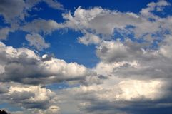 Clouds against a Blue Sky. White fluffy clouds in a bright blue sky Royalty Free Stock Photo