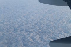 Clouds from a airplane view. A clear view of cottony clouds from a airplane. The blue and white create an abstract picture with its own unique landscape royalty free stock photos