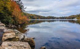Free Clouds Are Reflected In A Calm Minnewaska Lake In Orange County, NY, Surrounded By Bright Fall Foliage On A Partly Cloudy Day Stock Photos - 118997483