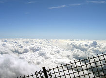 Clouds behind a fence. Over the clouds, the descending path from mount Fuji, looks like it's holding the clouds not to run Royalty Free Stock Photo