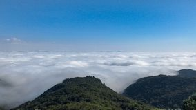 Clouds below the mountains. Blue sky royalty free stock photography