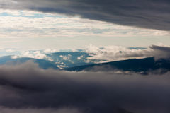 Clouds billow between hill and mountain landscape Stock Photo
