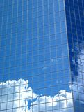 Clouds and Blue Building. Fluffy white clouds and blue skies reflected in a blue building royalty free stock photo