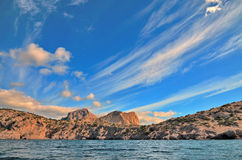 Clouds on a blue sky, the beautiful rocky mountains on the shores of the Black sea in Crimea. Royalty Free Stock Image