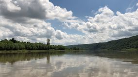 Clouds in the blue sky are displayed in the river.. Rafting on the Dniester River, the perfect combination of sky and water. On the horizon is a green shore stock video