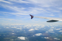 Clouds blue sky horizon and airplane wing. From above Stock Image