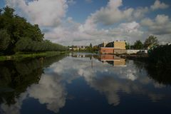 Clouds and blue sky mirrors in water of non frozen ice track in town Moordrecht Stock Images