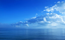 Clouds Blue Sky Ocean Background. A series of clouds forming over the ocean Stock Image