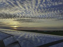 Clouds and blue sky reflecting on airplane wing at sunset royalty free stock photo