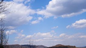 White clouds on a blue sky against trees and mountains in early spring. Clouds in the blue sky in the spring on a warm day on the background of the beginning to stock video footage