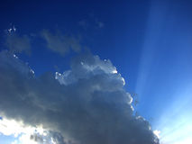 Clouds and a blue sky and sunbeam shining through Stock Image