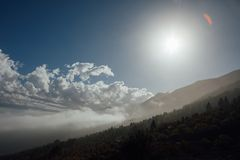 Clouds on blue sky with sunshine in mountains. Copy-space background Royalty Free Stock Images