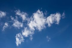 Clouds in the blue sky and the trail of the plane. White clouds in the blue sky and the trail of the plane Royalty Free Stock Photography