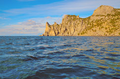 Clouds on a blue sky, the waves, the beautiful rocky mountains on the shores of the Black sea in Crimea. Royalty Free Stock Image