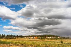 Clouds close the sun, storm clouds over the village stock photos
