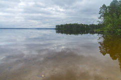 Clouds and coastal forest are reflected in the clear lake. Lake Pistayarvi on Pistayoki river, Karelia, Russia Royalty Free Stock Photography