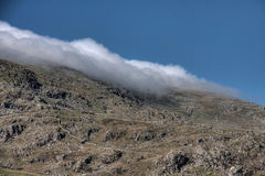 Clouds coming down the mountain Stock Photography