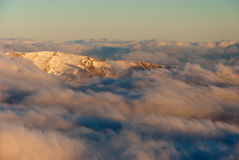 Clouds cover. A mountain peak rising over the clouds cover Stock Photo