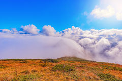 Clouds cover mountain tops at autumn day time. Royalty Free Stock Photo