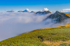 Clouds cover mountain tops at autumn evening time. Royalty Free Stock Photo
