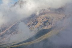 Clouds coverig rocks in mountains of Tien Shan Royalty Free Stock Image